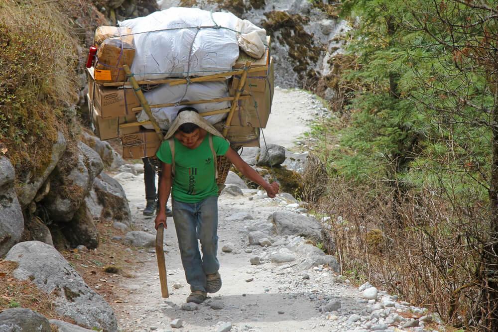 um sherpa a carregar varios fardos pela montanha acima