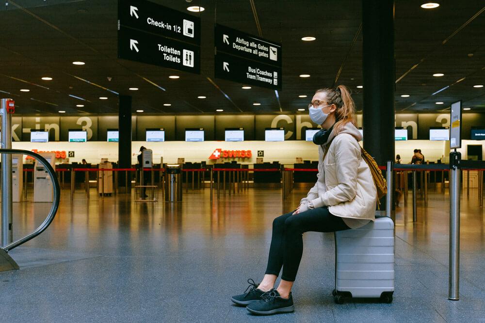 mulher de mascara espera num aeroporto