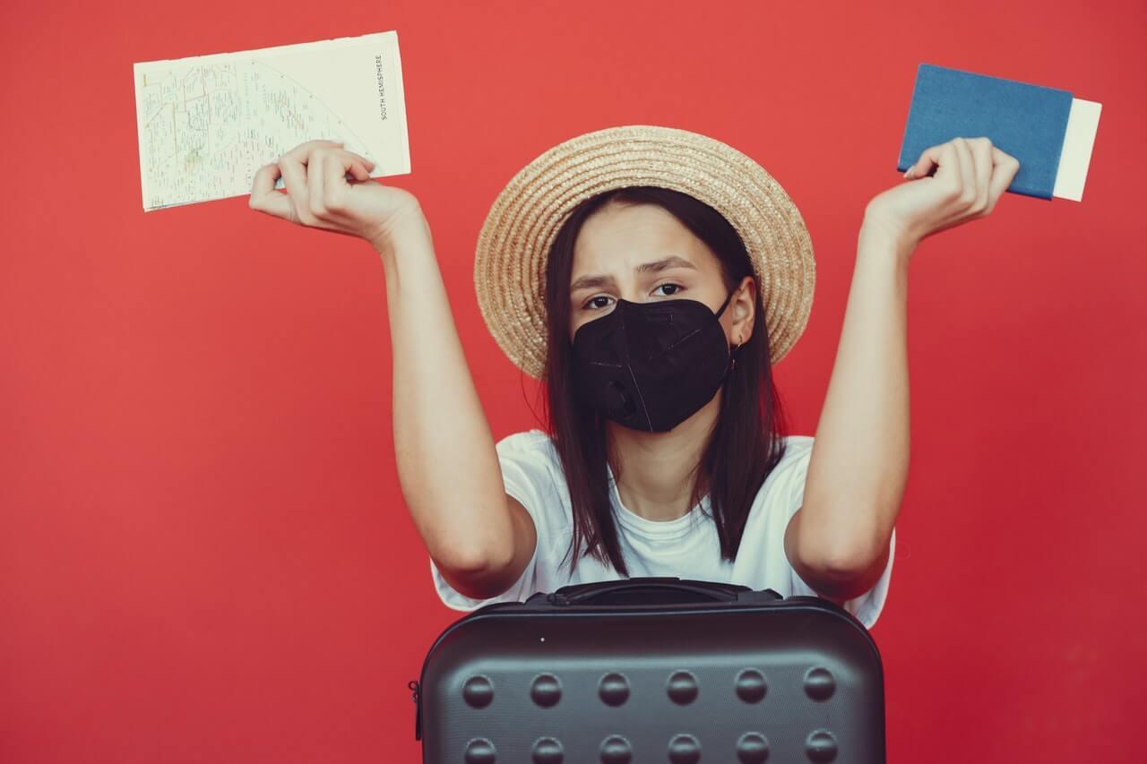 mulher com mascara, mala, passaporte e mapa pronta para viajar