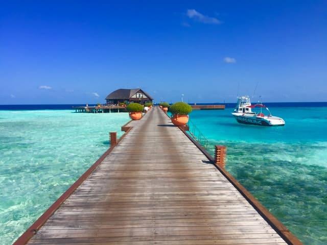 passagem sobre a água com barco e alojamento no horizonte, maldivas