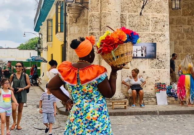 mulher com trajes coloridos e flores em cuba