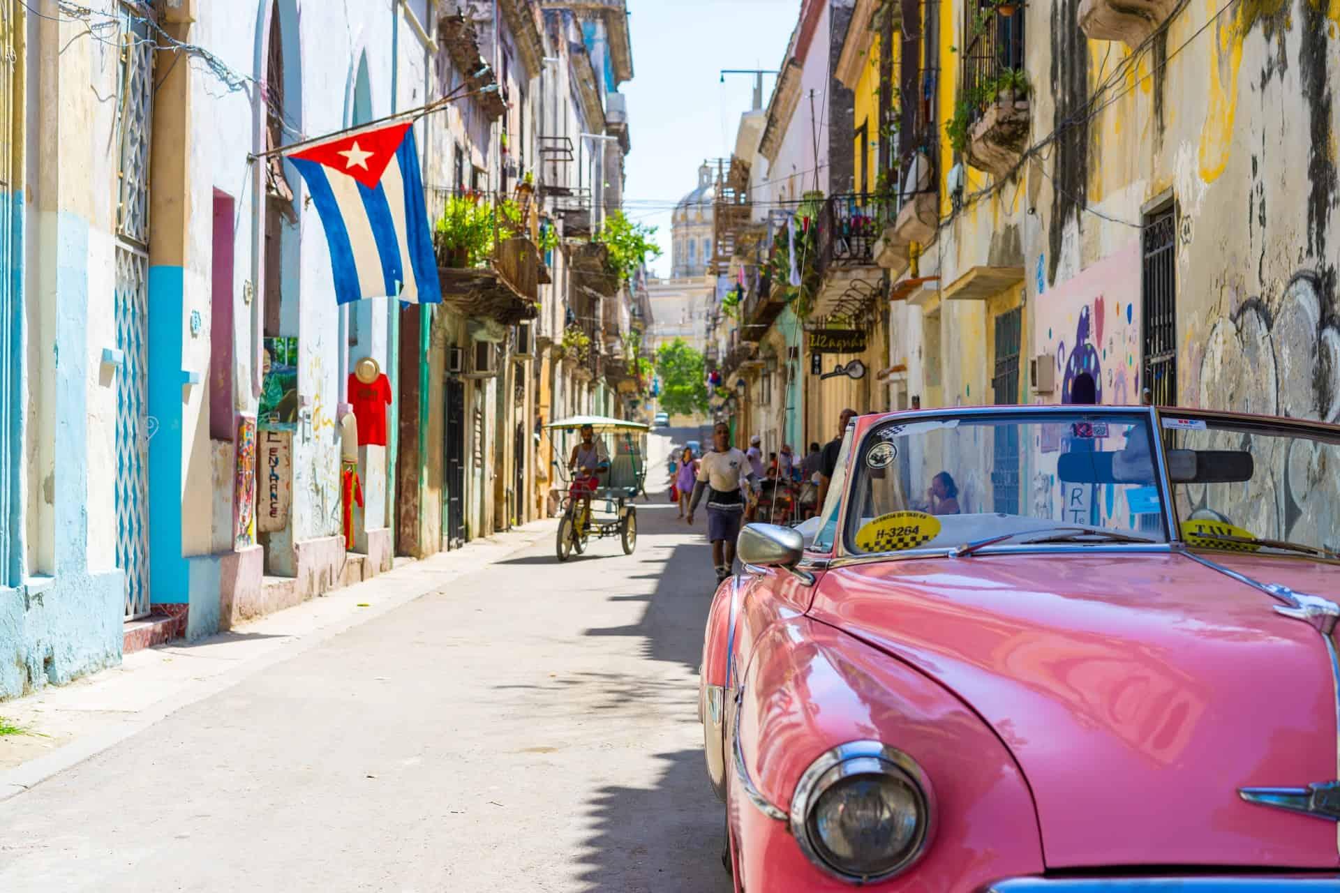 rua de cuba com carro clássico e bandeira