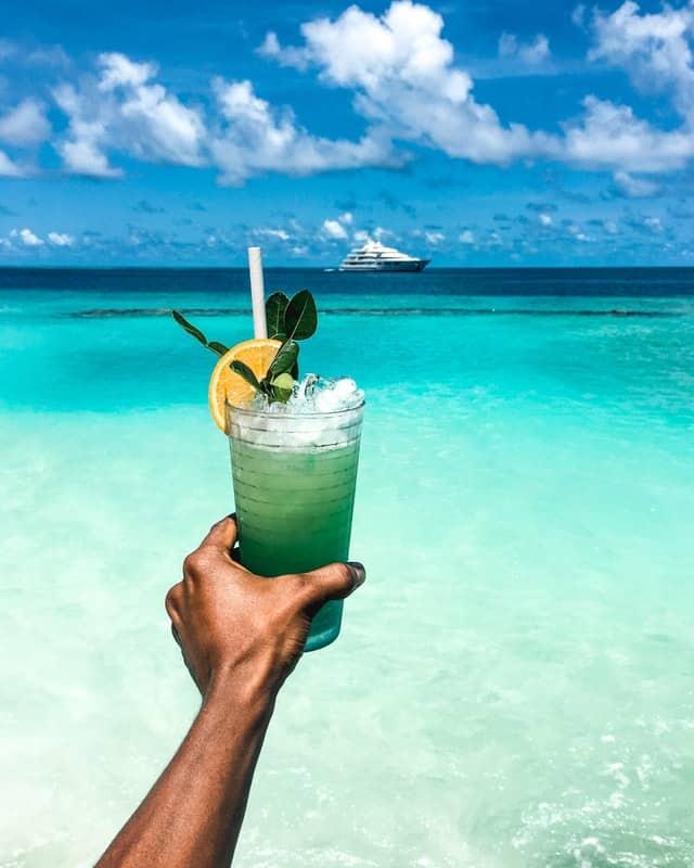 mao a segurar bebida com palhinha nas maldivas